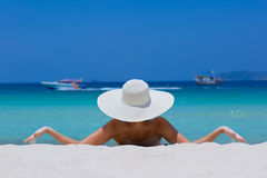 Woman in white hat lying on the beach. Blue sea and sky background stock photo