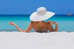 Woman in white hat lying on the beach. Blue sea and sky background stock images