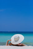 Woman in white hat lying on the beach. Blue sea and sky background royalty free stock photography