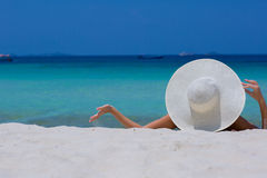 Woman in white hat lying on the beach. Blue sea and sky background Royalty Free Stock Photo