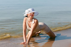 Woman in white hat posing against the sea Stock Photos