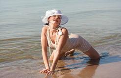 Woman in white hat posing against the sea Stock Photography