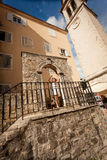 Woman in white hat posing on old stone stairs at city of Budva Stock Photography