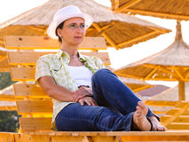Woman with white hat relaxing at sunset on beach Stock Photo