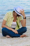 Woman with white hat sitting on beach Royalty Free Stock Image