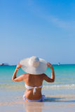 Woman in white hat sitting on the beach. Blue sea and sky background stock photo