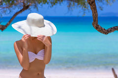 Woman in white hat standing on the beach. Blue sea and sky background royalty free stock photography