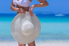Woman with white hat standing on the beach. Blue sea and sky background Royalty Free Stock Photos