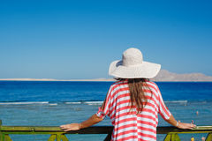 Woman in white hat standing next to the railing and looks at sea Stock Photo
