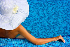 Woman with white hat in swimming pool Stock Photography