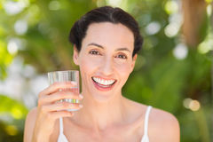 Woman in white having a glass of water Stock Images
