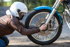 Woman in white helmet sitting on the kneels on the ground against motorbike spoked wheel, holding axis, repairing works Royalty Free Stock Photos