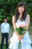 Woman In White Holding A Bouquet Of Pink Flowers Royalty Free Stock Images