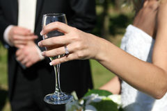 Woman in white holding a glass. Lady in a white dress holds a glass at a function Stock Photo