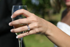 Woman in white holding a glass. Lady in a white dress holding a glass showing off her new wedding ring Stock Photos