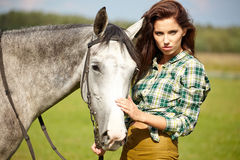 Woman with a white horse Stock Images
