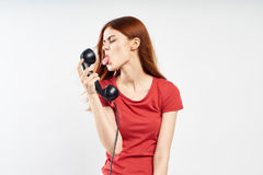 Woman on white isolated background shows the language of a landline phone, emotion, communication Royalty Free Stock Images