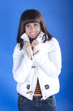 Woman in a white jacket on a blue background stock photos
