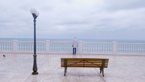 Woman in white jacket and hood on beautiful terrace with sea view on waterfront. Back view. stock footage