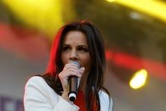 Woman in white jacket and orange shirt singing Stock Photos
