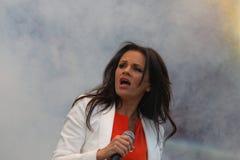 Woman in white jacket and orange shirt singing Stock Photo