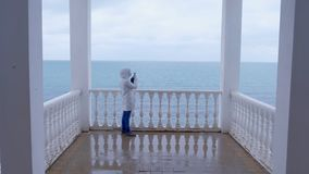 Woman in the white jacket shoots sea waves video on smartphone on beautiful terrace with sea view. Back view. stock video