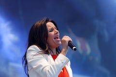 Woman in white jacket singing Stock Photo