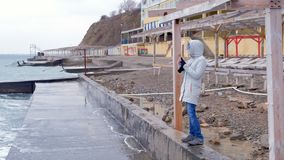 Woman in a white jacket takes a mobile phone big storm waves standing on embankment. Side view. Woman in a white jacket takes a mobile phone big storm waves stock footage