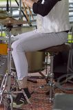 Woman in white jeans and sneakers plays the drum set stock photos