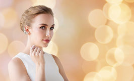 Woman in white with jewelry over holidays lights Royalty Free Stock Images
