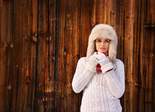 Woman in white knitted sweater with cup near rustic wood wall Royalty Free Stock Images