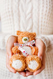 Woman in white knitted sweater holding christmas toy bear Stock Photography
