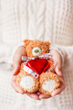 Woman in white knitted sweater holding toy teddy bear Royalty Free Stock Images