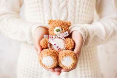 Woman in white knitted sweater holding toy teddy bear Royalty Free Stock Photo