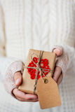 Woman in white knitted sweater and mitts holding a present. Stock Images