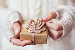 Woman in white knitted sweater and mitts holds a present. Stock Photography