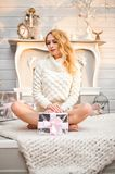 Woman in a white knitted sweater sitting with gift box Stock Image
