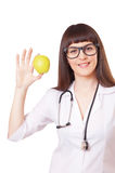 Woman in a white lab coat with apple Stock Images