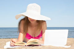 Woman with white laptop and book on the summer beach. Young woman with white laptop and book on the summer beach Stock Photo