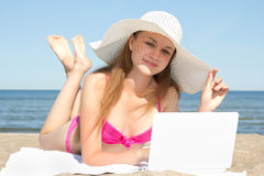 Woman with white laptop on the summer beach. Young woman with white laptop on the summer beach Royalty Free Stock Photo