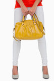 Woman in white leggings holding yellow bag Royalty Free Stock Photo