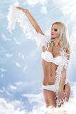 Woman in white lingerie as angel on the clouds Stock Image