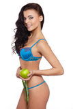 Woman in white lingerie with green apple measuring Royalty Free Stock Images