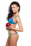 Woman in white lingerie with red apple measuring Royalty Free Stock Photo