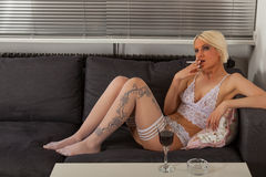 Woman in white lingerie on the sofa Stock Image