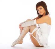 Woman in white lingerie. Young brunette woman in white lingerie - stockings, garter belt, panties Royalty Free Stock Images