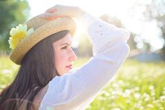 Woman in White Long Sleeve Shirt Wearing a Straw Hat during Daytime at Flower Field Royalty Free Stock Photo