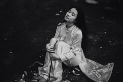 Woman in White Long Sleeve Top Sitting on the Ground Royalty Free Stock Images