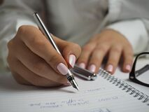 Woman in White Long Sleeved Shirt Holding a Pen Writing on a Paper Royalty Free Stock Images