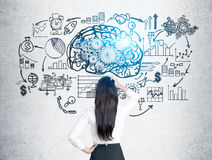 Woman in white looks at brain with gears. Rear view of a woman with black hair scratching her head and looking at a brain with gears sketch drawn on a concrete Royalty Free Stock Photos